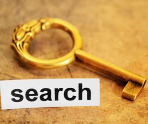 A picture of a gold key with search text